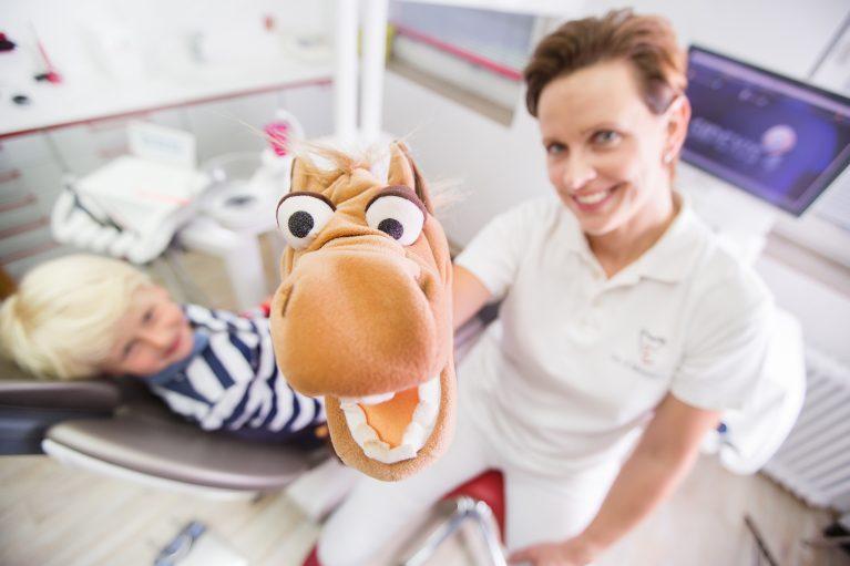 Dr. Verena Mönnich nimmt Kind mit Pferdehandpuppe die Angst vor der Zahnbehandlung