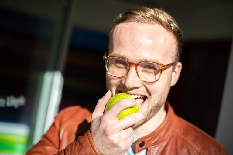 Junger Mann beißt in grünen Apfel