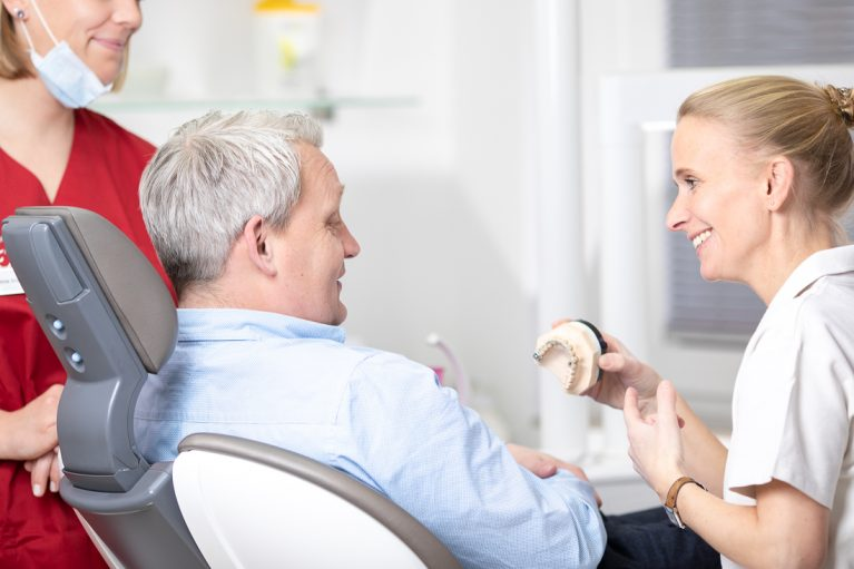 Dr. Melanie Orwat zeigt männlichem Patient Möglichkeiten für Zahnersatz auf
