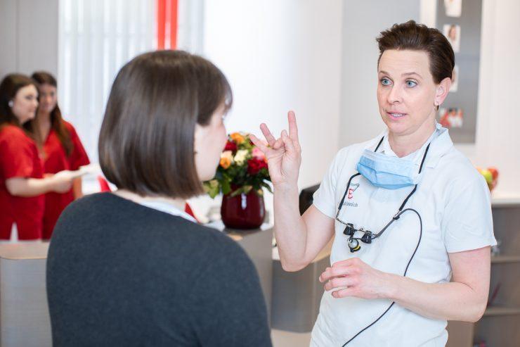 Dr. Verena Mönnich erklärt einer Patientin die Behandlung in Gebärdensprache