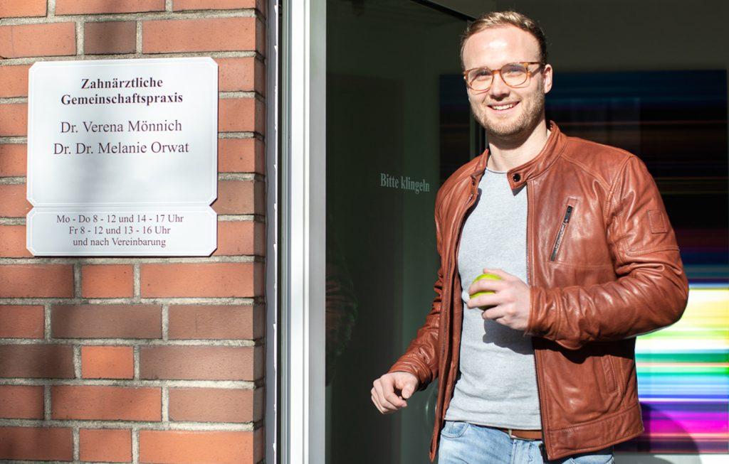 Junger männlicher Patient verläßt lächelnd die Recklinghausen Zahnarztpraxis