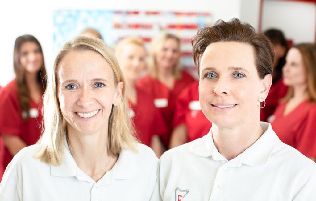 Dr. Verena Mönnich und Dr. Dr. Melanie Orwat mit dem Zahnarztpraxisteam im Hintergrund